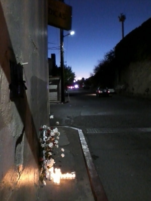 Photo of sidewalk with flowers and candles in the shape of a cross overlooked by border wall and surveillance tower